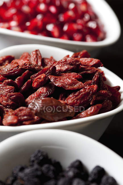 Closeup view of dried goji, pomegranate seeds and chokeberries in bowls — Stock Photo