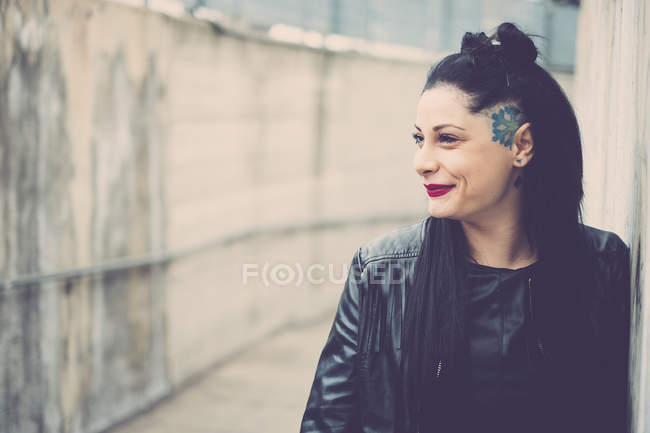 Smiling dark-haired young woman with black leather jacket and tattoos — Stock Photo