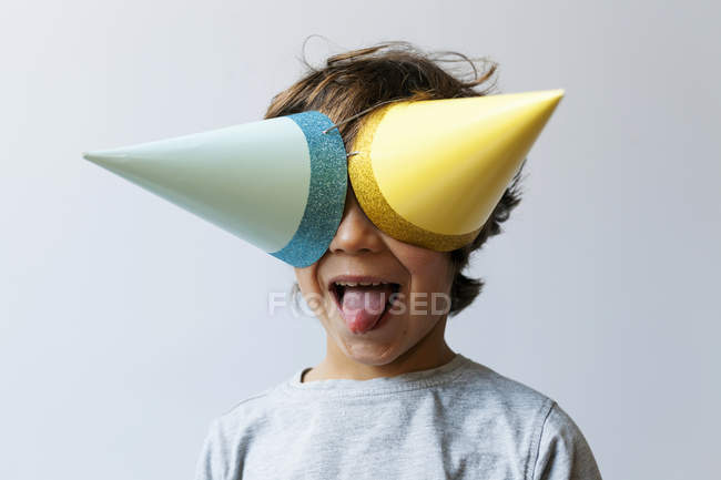 Portrait of boy in party hats on face showing tongue — Stock Photo