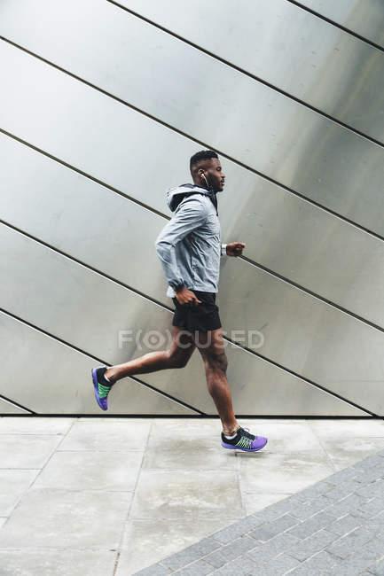 Молода людина, що біжить в міському районі — стокове фото