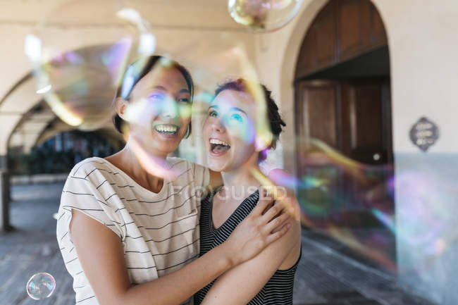 Two young women playing with soap bubbles — Stock Photo
