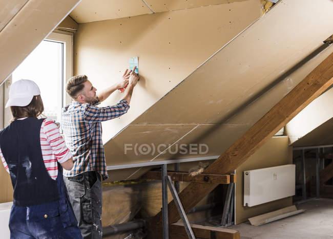 Портрет молодой пары, ремонтирующей чердак — стоковое фото