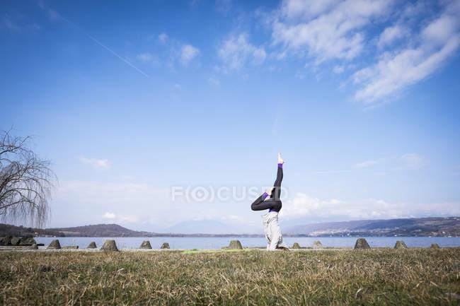 Pratica yoga facendo un headstand in un lago della donna — Foto stock