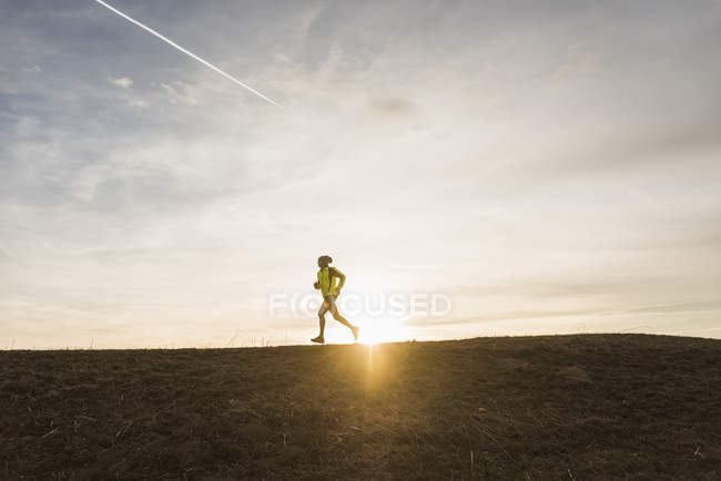 Portrait of young man running in field — Stock Photo