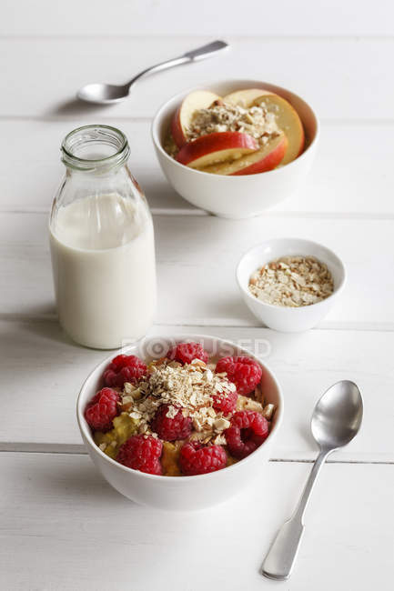 Closeup view of oat flakes with raspberries, sliced apple and milk — Stock Photo