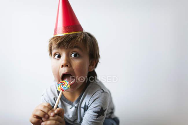 Портрет мальчика в шляпе с леденцом на лице — стоковое фото