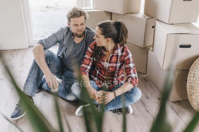 Casal sentado no chão ao lado de caixas móveis — Fotografia de Stock