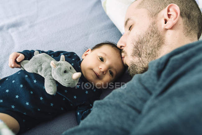 Father kissing newborn baby girl head on bed — Stock Photo