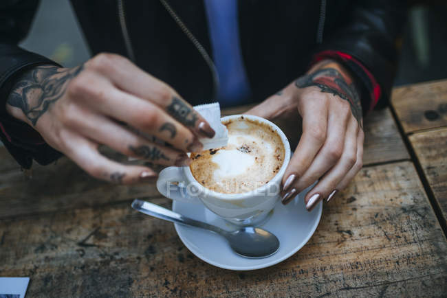 Closeup of female hands pouring sugar into a coffee — Stock Photo