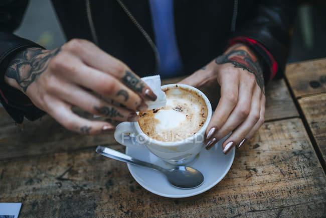 Closeup de mãos femininas, despejando um café com açúcar — Fotografia de Stock
