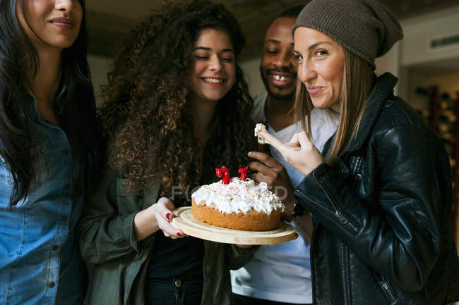 Portrait of young friends standing with birthday cake — Stock Photo