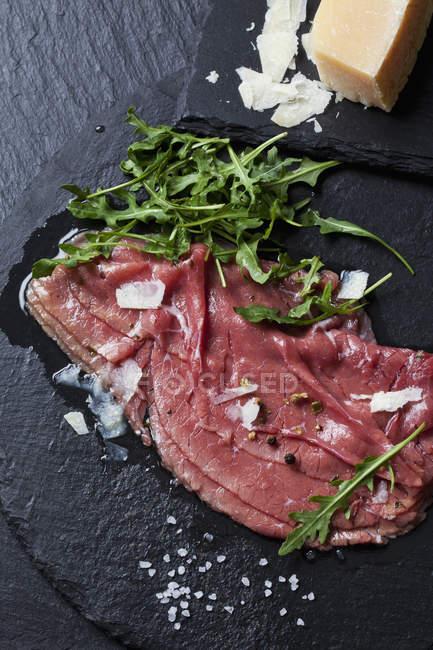 Крупным планом вид сырья говядины с сыром пармезан и ракета — стоковое фото