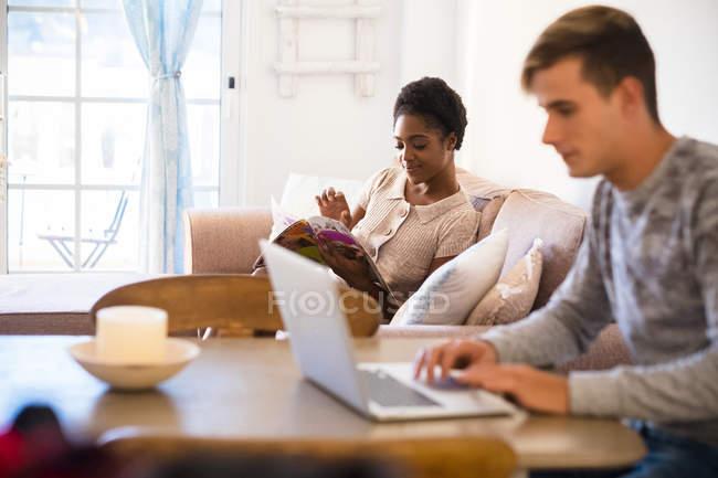 Attraktives multikulturelles junges Paar zu Hause, Mann mit Laptop — Stockfoto