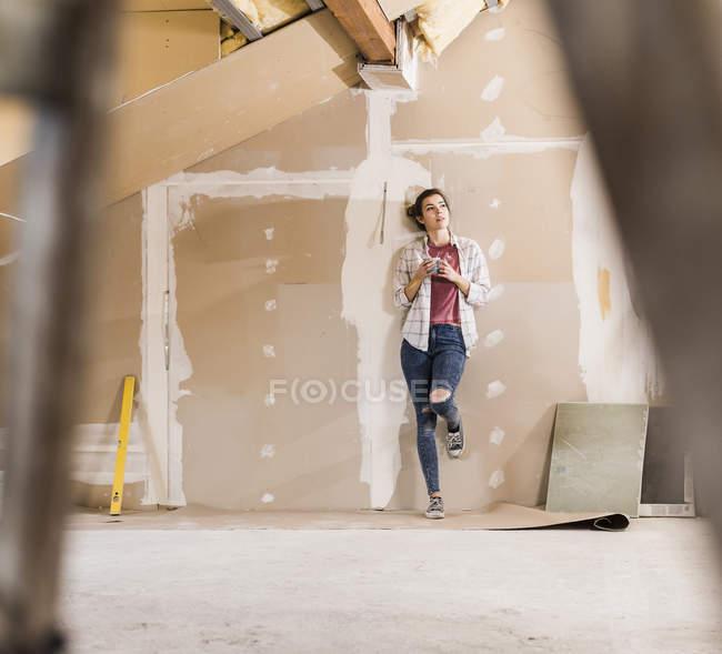 Портрет молодой женщины, стоящей с чашкой у стены — стоковое фото