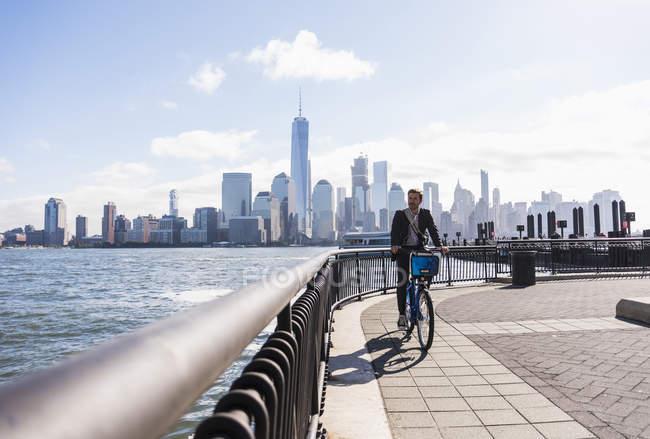 Homme à vélo au bord de l'eau du New Jersey avec vue sur Manhattan, New York, États-Unis — Photo de stock