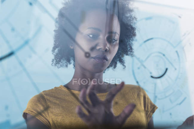 Young woman using transparent touchscreen display — Stock Photo