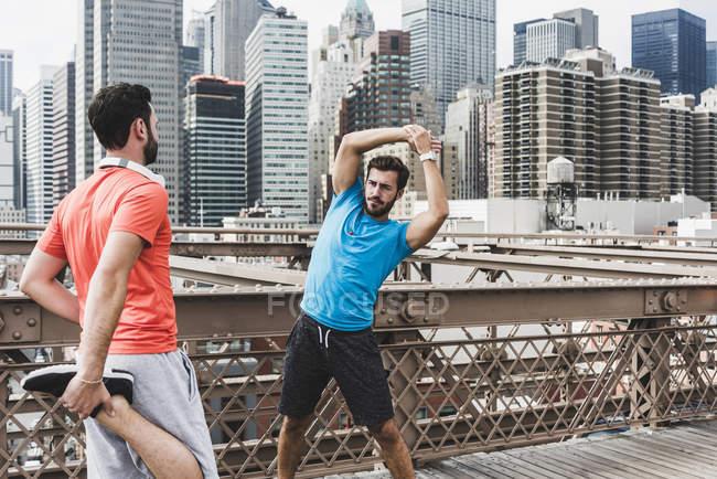 USA, New York, Brooklynbridge, zwei junge Männer am Fitness-Training, Stadtansicht Blick auf Hintergrund — Stockfoto