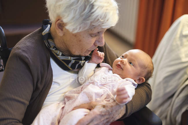 Old caring woman holding great-granddaughter — Stock Photo