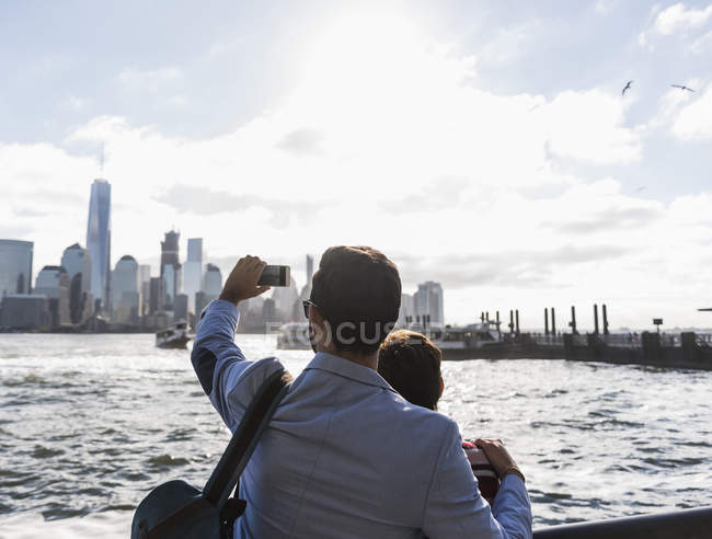 USA, New York,New Jersey, Adults at the waterfront taking photo Manhattan cityscape — Stock Photo