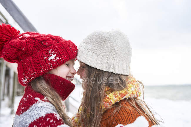 Two sisters having fun in winter and hugging — Stock Photo