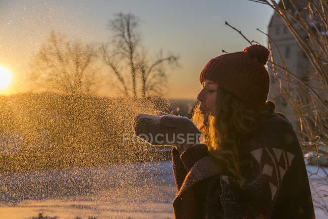 Giovane donna che soffia neve al tramonto — Foto stock