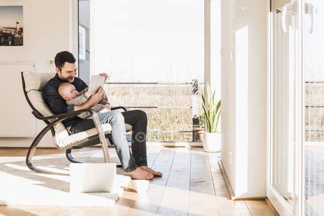 Father sitting in armchair with baby son on lap and using mobile devices — Stock Photo