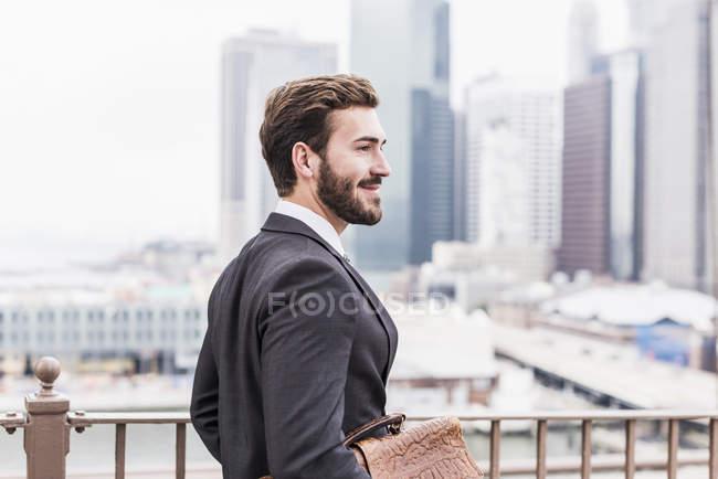 Портрет молодого бизнесмена с папкой документов, вид сбоку — стоковое фото