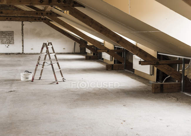 Daytime view of ladder and bucket in attic — Stock Photo