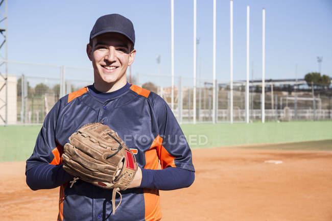 Portrait du joueur de baseball avec un gant de baseball de sourire — Photo de stock