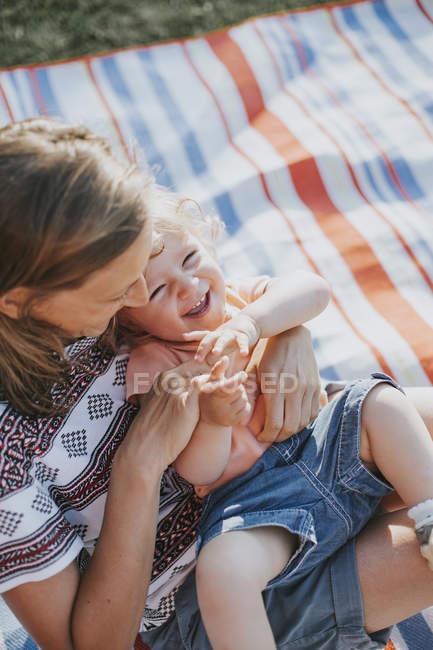 Mère chatouillant petite fille sur couverture — Photo de stock