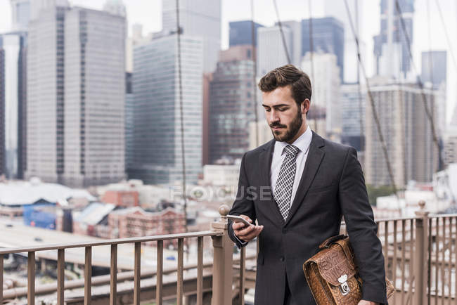 Соединенные Штаты Америки, New York, Brooklyn bridge, young businessman on phone, cityscape on background — стоковое фото