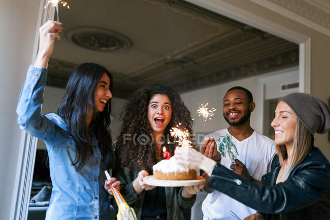 Portrait of young friends celebrating birthday with cake and sparklers — Stock Photo