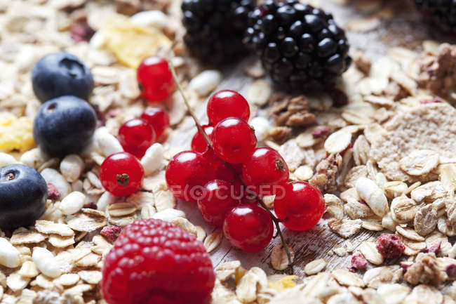 Closeup view of oat flakes with berries on wood — Stock Photo