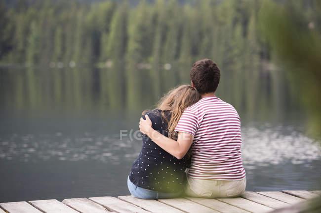 Giovane coppia seduta su un molo al lago — Foto stock