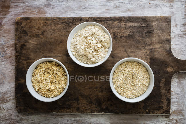Top view of different sorts of oat flakes in bowls — Stock Photo