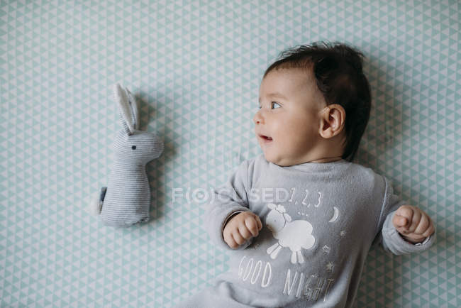 Happy baby girl lying on crib with a rabbit shaped toy — Stock Photo