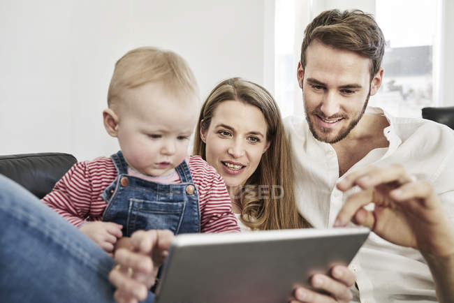 Genitori con bambina guardando tablet sul divano — Foto stock