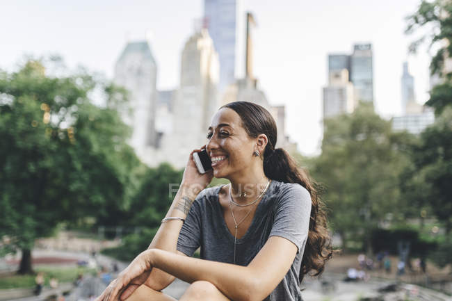 Portrait of woman using smartphone in park — Stock Photo
