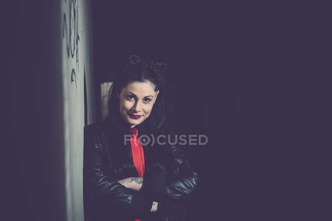 Portrait of smiling young woman leaning against wall in underpass — Stock Photo