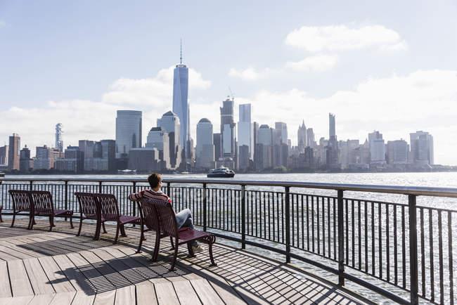 Жінка, сидячи на лавці в Нью-Джерсі набережній з видом на Манхеттен, США — стокове фото