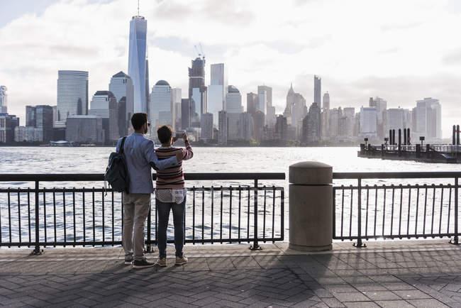 USA, New York, New Jersey, Adulti al lungomare scattando foto Manhattan city scape — Foto stock