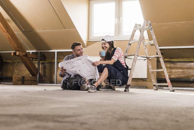 Портрет молодої пари, дивлячись на план будівництва — стокове фото