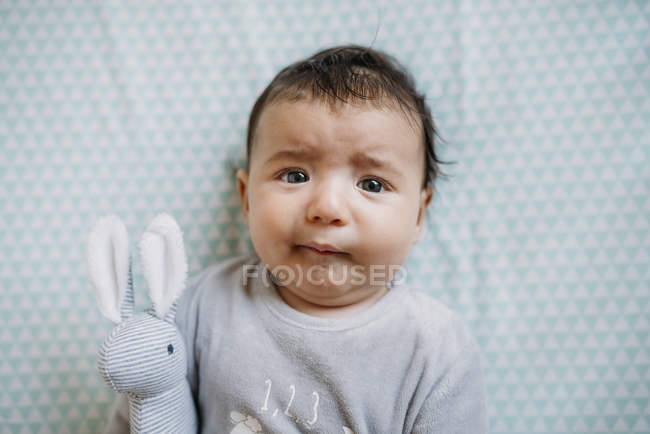 Baby girl lying on crib with funny worried face and holding stuffed rabbit — Stock Photo