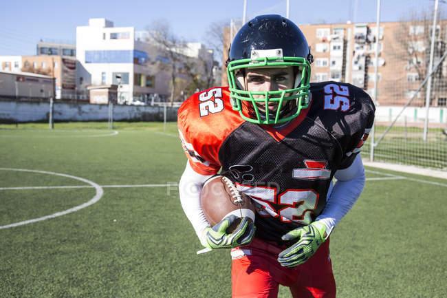 Американский футболист держит мяч во время матча — стоковое фото
