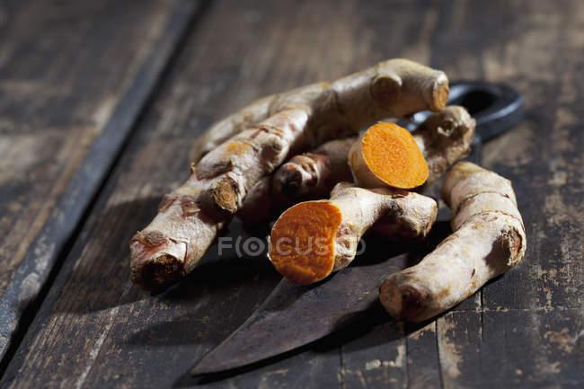 Vista de closeup de raízes de curcuma e faca forjada na superfície de madeira escura — Fotografia de Stock