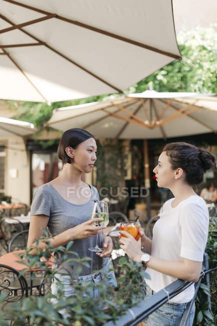 Две молодые женщины, говорить вместе в кафе sidewalk с питьевой очки — стоковое фото