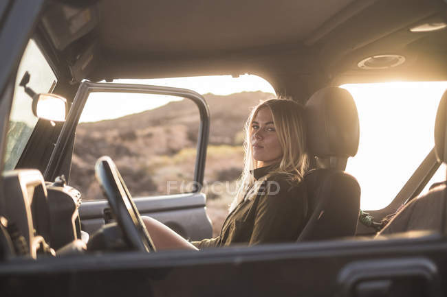Woman sitting in car at sunset and looking at camera — Stock Photo