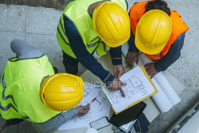 Група працівників, які говорять про проект на робочий стіл, видно з вище. — стокове фото