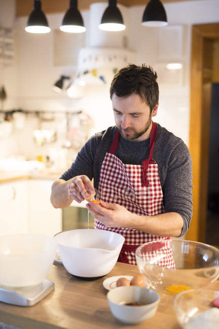 Man standing in kitchen and preparing cake dough — Stock Photo