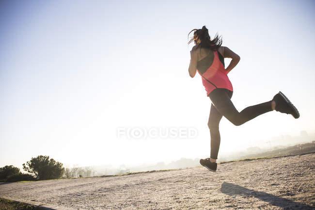 Молода жінка працює при сонячному світлі на шлях — стокове фото